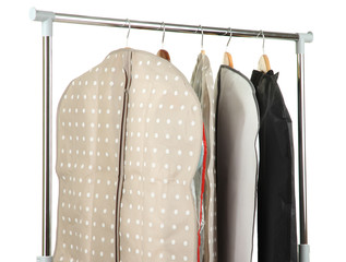 Clothes in cases for storing on hangers, on gray background