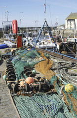 fishing nets and buoys with harbour scene at Pittenweem