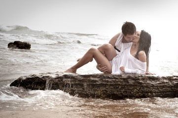 Young beautiful couple kissing on beach rocks