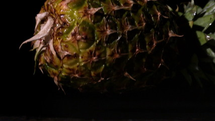 Pineapple falling and splitting on black background