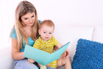 Mother and son reading book on sofa at home