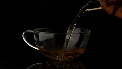Tea pouring from teapot in glass cup