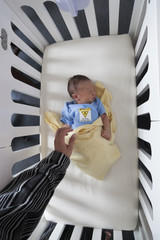 High angle view of a newborn baby sleeping in a crib
