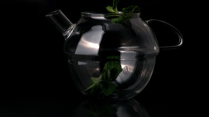 Mint leaves falling into glass teapot