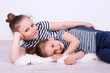 Beautiful small girls lying on floor on wall background