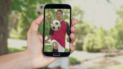Hand showing girls playing football clips on smartphone
