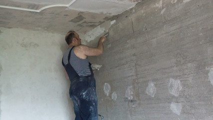 Apartment renovation. The man plasters a wall