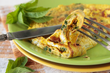 Piece of omelette with goutweed