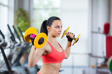 Woman in gym sport exercising with dumbbells