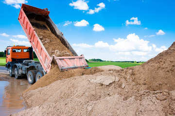Dumper truck unloading soil in water during road works