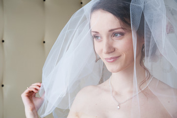 Smiling happy bride with white veil