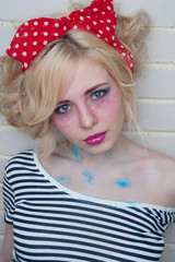 Woman near wall. Professional modern make-up. Pinup style