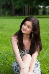 Girl sits in Park on grass field