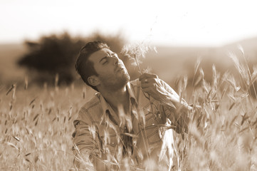 Fashion sepia portrait of attractive man blowing dandelion