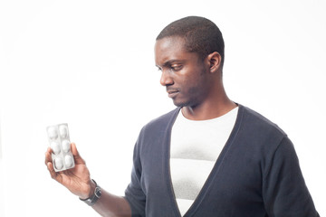 Cassual dressed black man with pack of pills. Isolated on white.