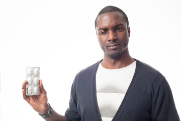 worried cassual dressed black man with pack of pills