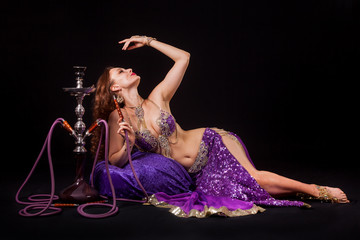 Belly dancer posing with hookah