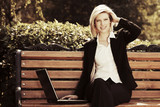 Happy business woman with laptop in a city park