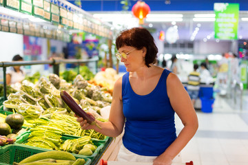 woman buys eggplant