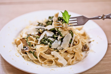 Delicious vegetarian dish of pasta and parsley on wooden table