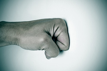 man fist punching a white surface