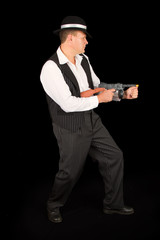 Dangerous gangster with 1920 style clothes standing with gun