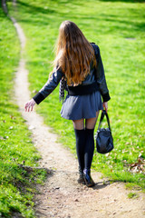 Woman walking on a footpath in the park