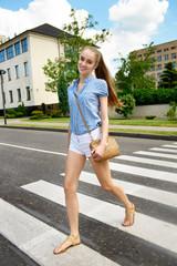 Woman crossing the street on the crosswalk