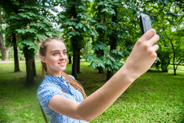 beautiful woman shooting selfie on mobile phone in the park