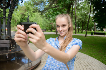 woman shooting selfie on mobile phone in the park