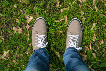 Man in gum shoes standing on the green grass