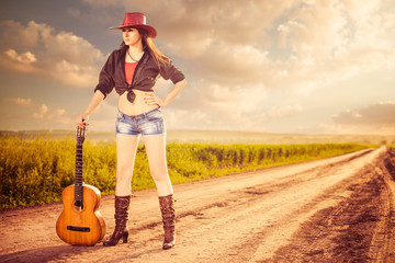 sexy cowgirl with guitar at rural sunset road