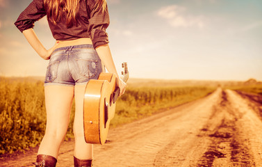 woman in shorts with old guitar on road to horizon