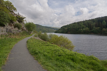 Footpath alongside a picturesque lake, with wooded hills