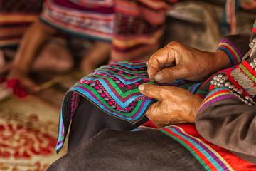 Female Hand stitching cloth to make ancient Thai pattern fabric