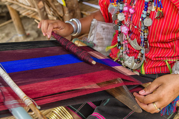 Woman working at the loom. thai national crafts. Focus on the fa