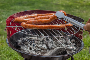 Man Preparing Sausage on Grill