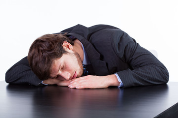 Tired businessman sleeping on table