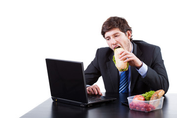 Hungry businessman eating a sadwich