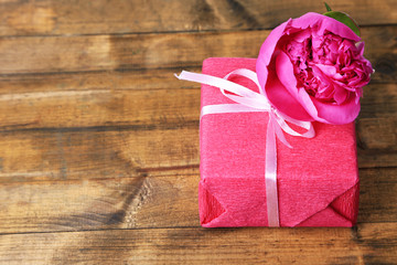 Pink gift with bow and flower on wooden table close-up