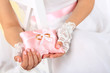 Bride in white dress and gloves holding decorative pillow with