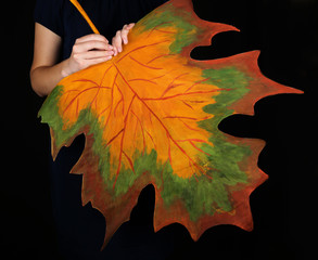 Girl holding decorative maple leaf on black background