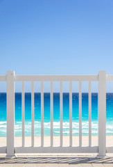 White fence and blue ocean on a tropical beach