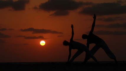 Silhouette of a beautiful Yoga couple