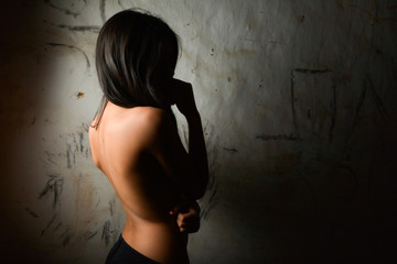 Studio portrait of naked back of woman in dark with hidden face
