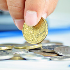 Fingers picking up a coin - one Australian dollar (AUD)