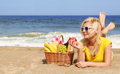 Picnic on the Beach. Blonde Young Woman with Basket of Food