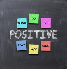 stay positive advice with adhesive notes on blackboard