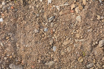Abstract dirty sand background with stones, closeup shot.