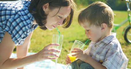 Mother and son outdoors drinking juice and smiling. Ultra HD 4K
